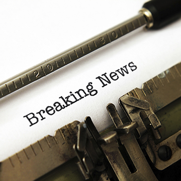 """typewriter showing the words typed """"Breaking News"""""""