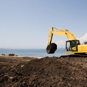 Construction vehicle moving dirt on the top of a cliff edge