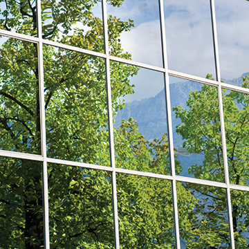 square window panels with reflection of trees and blue skies