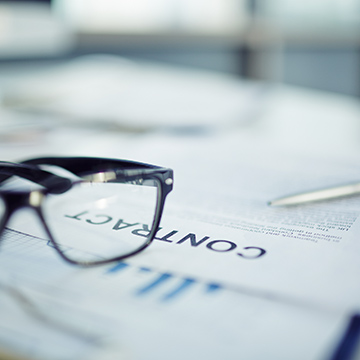 A pair of eyeglasses (only one lens visible) sitting on top of paperwork