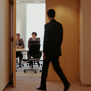 Man walking into Conference Room through double doors for a meeting, 2 other men in the room already