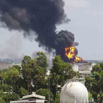 Oil refinery explosion, black smoke in the sky