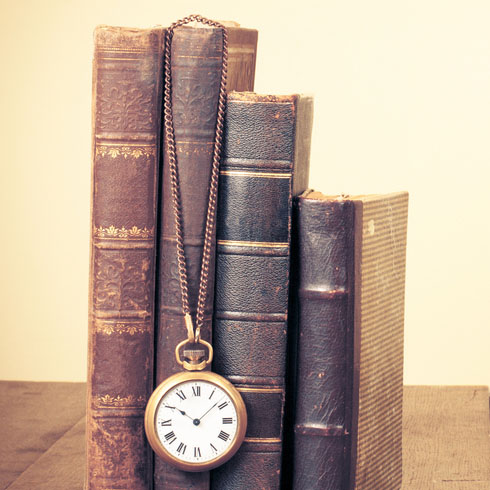 Vintage Books upright with antique pocket watch hanging from them