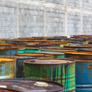 a group of rusty metal barrels with paint splashed on them